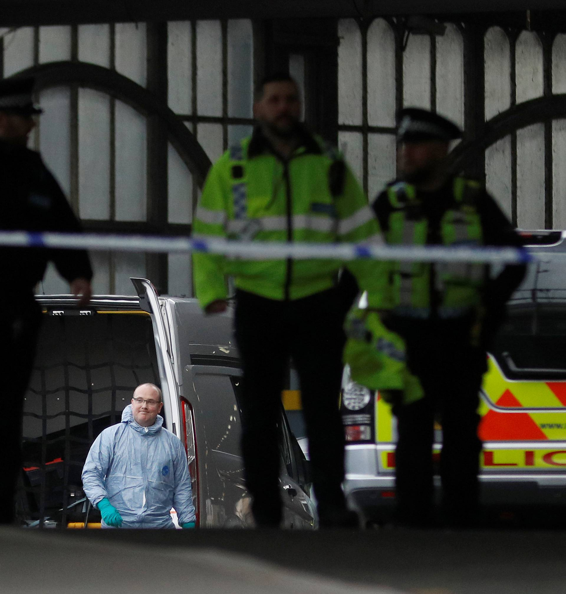 Police officers including one wearing a forensic suit, are seen in a cordoned off area at Waterloo station near to where a suspicious package was found, in London