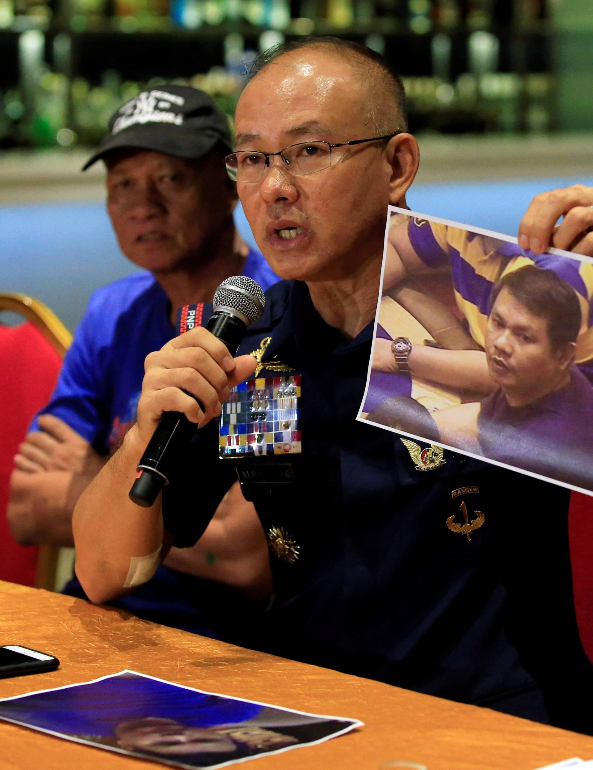 Oscar Albayalde, chief of the capital's police office, shows to journalists a picture of a gunman during a press briefing at a hotel in Pasay city, metro Manila