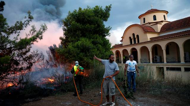 People try to extinguish a wildfire burning next to a church in the town of Rafina, near Athens