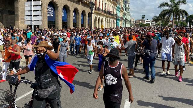 People walk during protests against and in support of the government, in Havana