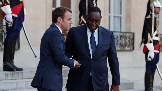 French President Emmanuel Macron accompanies Senegalese President Macky Sall as he leaves the Elysee Palace in Paris