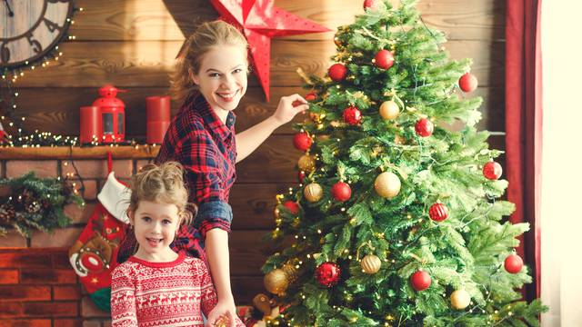 happy family mother and child girl decorated Christmas tree