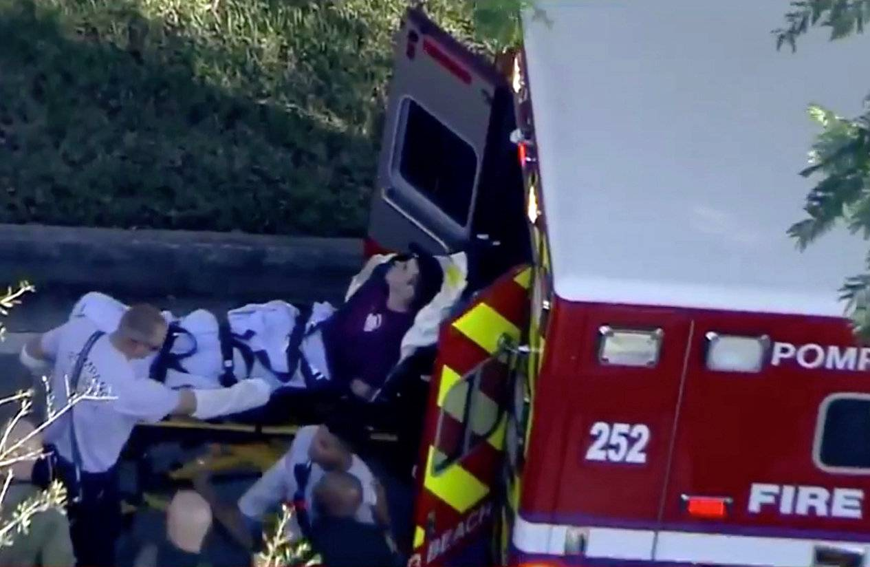 A man who was placed in handcuffs by police is loaded into a paramedic vehicle after a shooting incident at Marjory Stoneman Douglas High School in Parkland