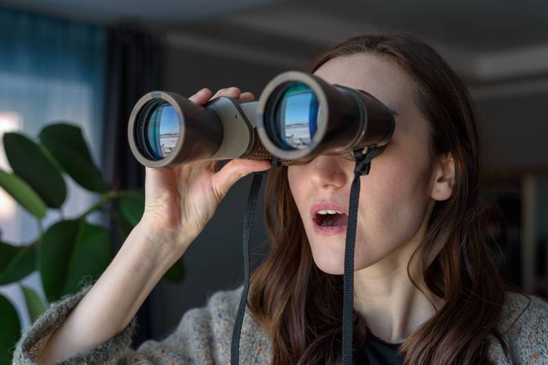 Portrait of a surprised brunette with binoculars looking out the window, spying on neighbors