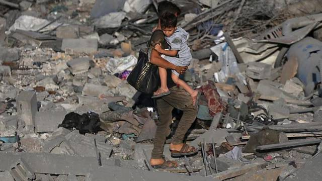 Palestinian boy carries his brother as he walks through the debris of a house destroyed in an Israeli air strike in the southern Gaza Strip