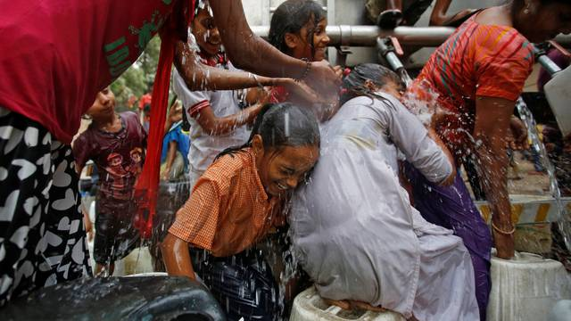 Girls get drenched as they struggle to fill empty containers with water from a municipal tanker on a hot summer day in New Delhi