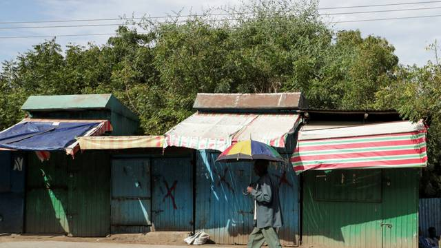 A man holds an umbrella as he walks past closed shops in Sanja, Amhara region near a border with Tigray