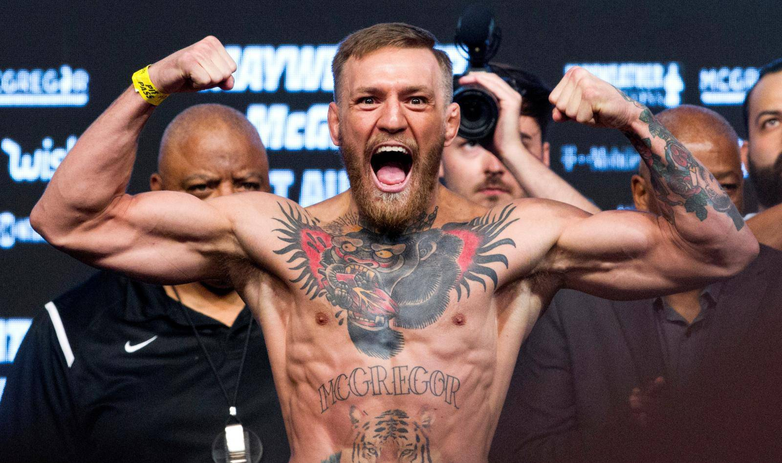 FILE PHOTO: UFC lightweight champion Conor McGregor of Ireland poses on the scale during his official weigh-in at T-Mobile Arena in Las Vegas