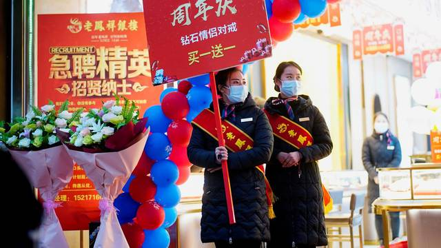 Sales assistants of a jewellery store wear face masks while doing promotions at a main shopping area almost a year after the global outbreak of the coronavirus disease (COVID-19) in Wuhan