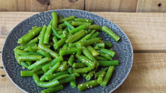 Plate with cooked green beans on wooden background