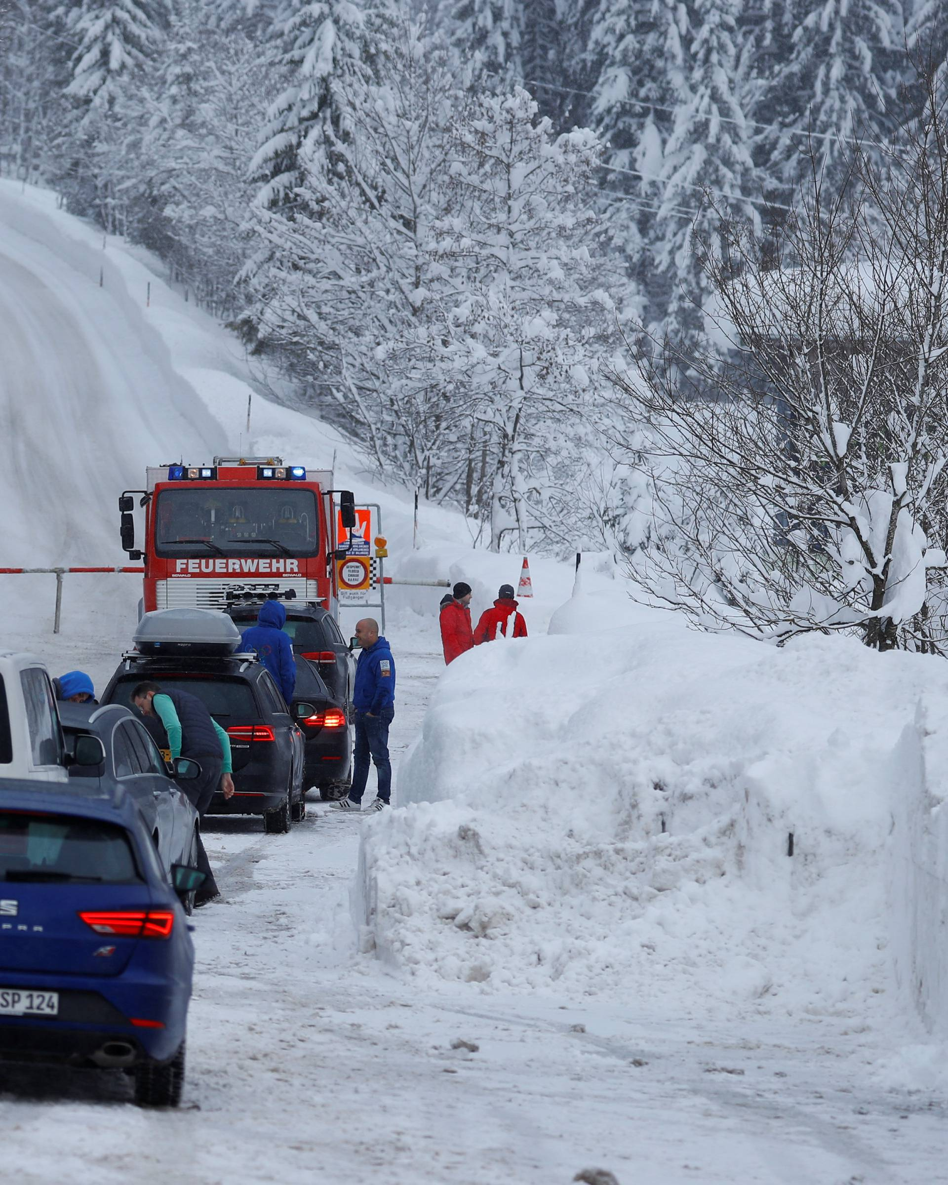 Tourists wait on a closed road after heavy snowfall near Obertauern