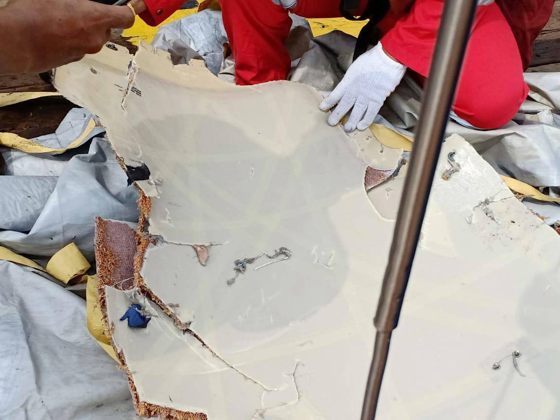 Workers of PT Pertamina examine recovered debris of what is believed from the crashed Lion Air flight JT610, onboard Prabu ship owned by PT Pertamina, off the shore of Karawang regency