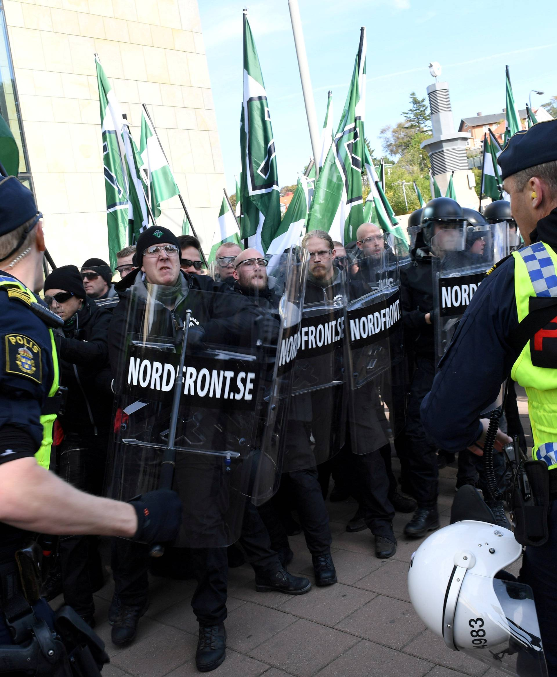 Police officers stop NMR demonstrators from trying to walk along a forbidden street during the Nordic Resistance Movement march in central Gothenburg