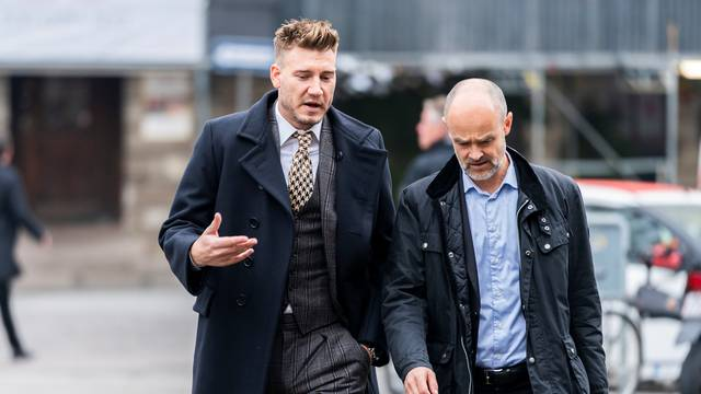 Denmark striker Nicklas Bendtner and lawyer Anders Nemeth arrive at the Copenhagen City Council