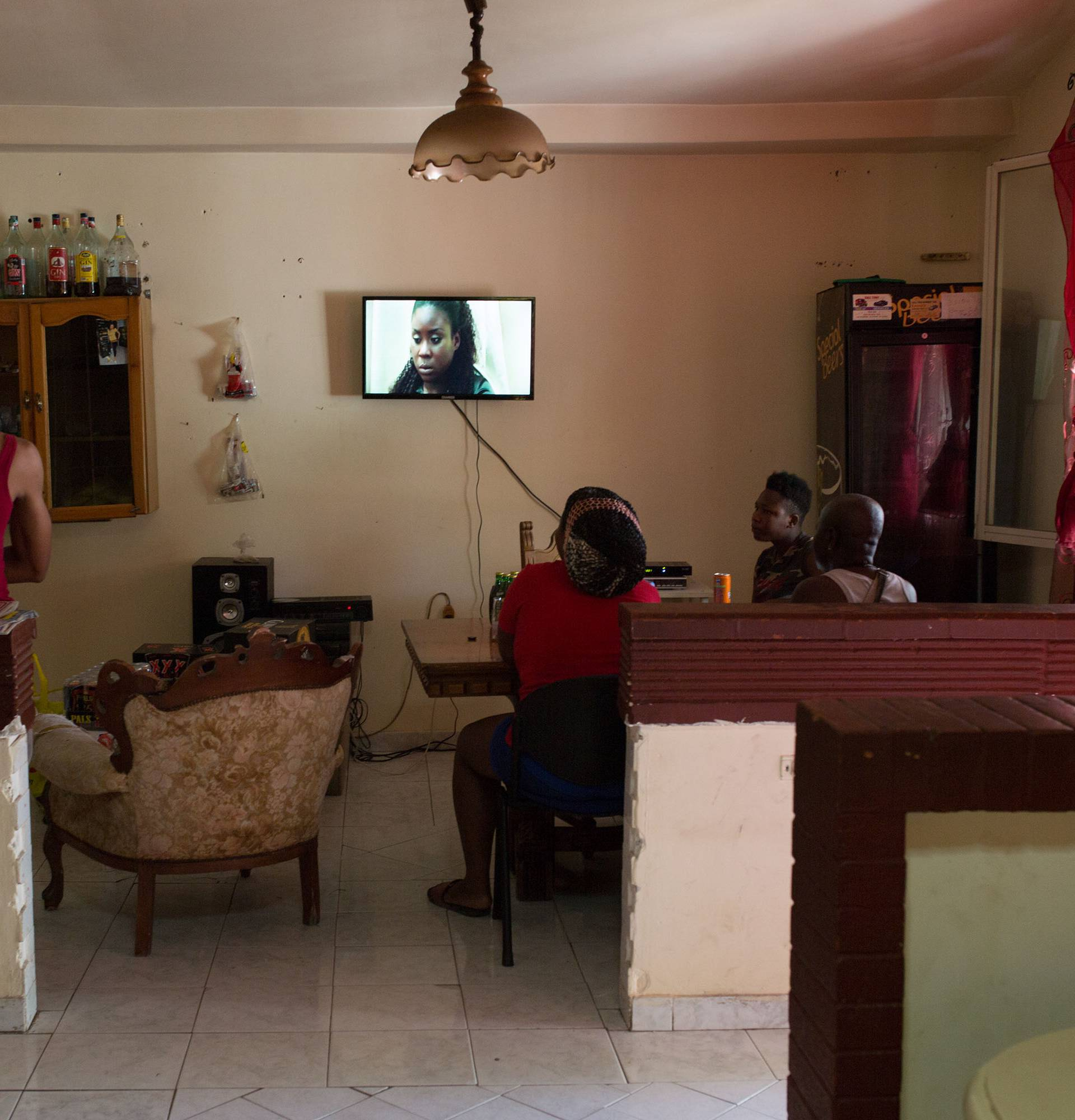 Migrants watching a TV series on Nigerian channel ROK in a connection house in Castel Volturno, Italy on August 23, 2018. Thomson Reuters Foundation / Valerio Muscella