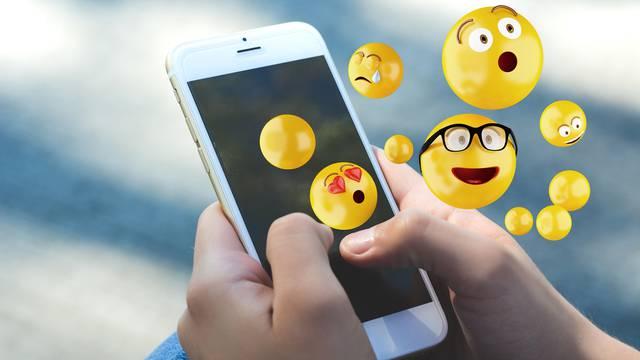 Woman using smartphone sending emojis.