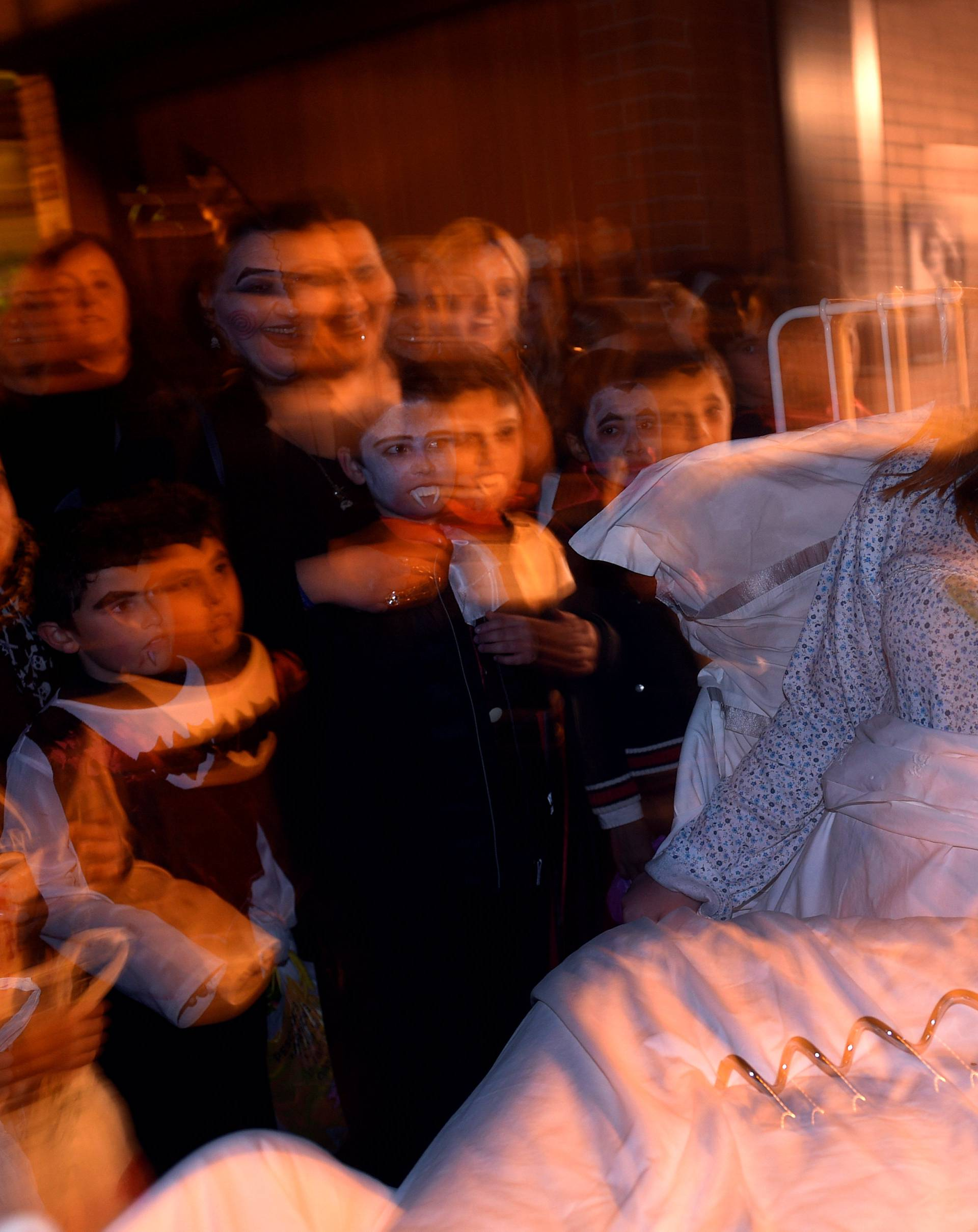 """A woman dressed up as a character from the movie """"The Exorcist"""" reacts during Halloween in La Fresneda"""