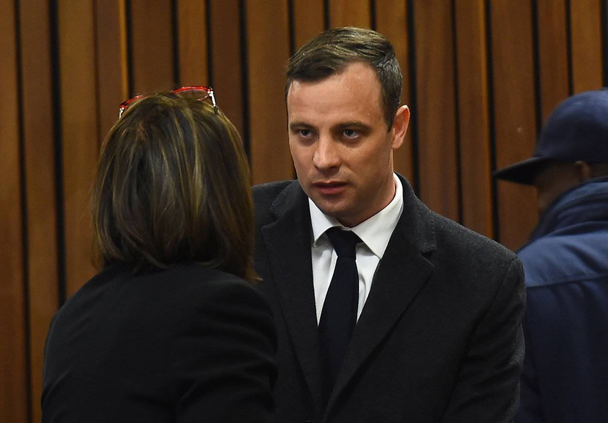 Olympic and Paralympic track star Oscar Pistorius speaks with his lawyer Barry Roux ahead of his sentence hearing at the North Gauteng High Court in Pretoria