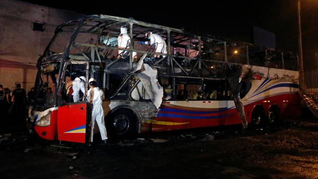 Peruvian investigators work next to a burnt bus on a street in Lima