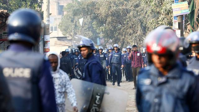 Policemen are seen patrolling the street while garments workers are protesting for higher wages at Ashulia, outskirt of Dhaka