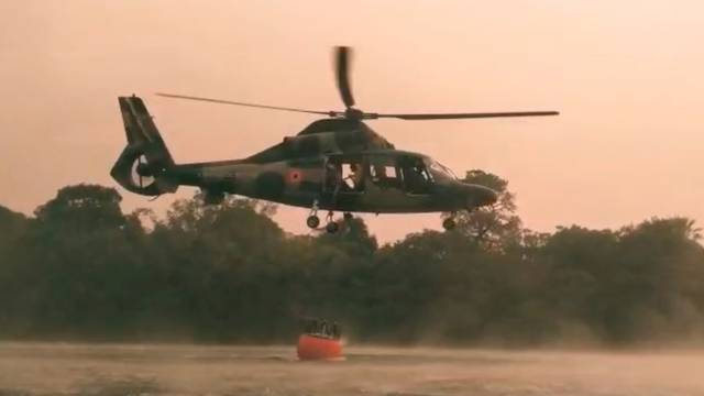 A Bolivian Air Force helicopter collects water to fight forest fire, near Robore