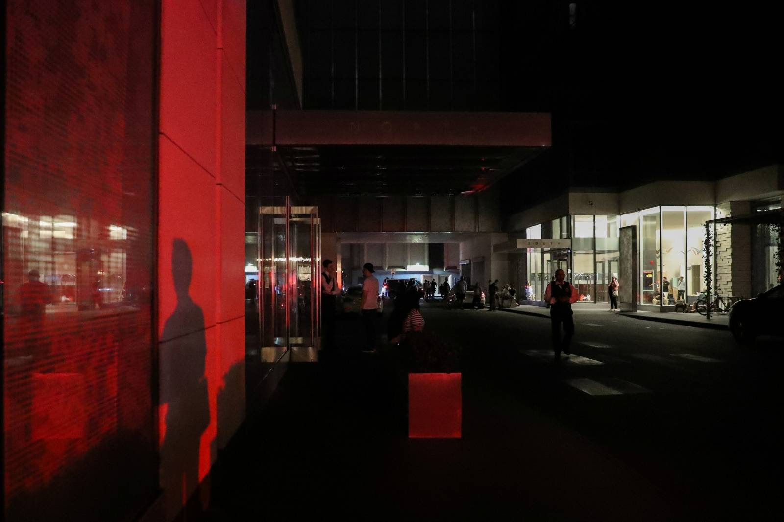 People sit outside their residential building near Times Square area, as a blackout affects buildings and traffic during widespread power outages in the Manhattan borough of New York