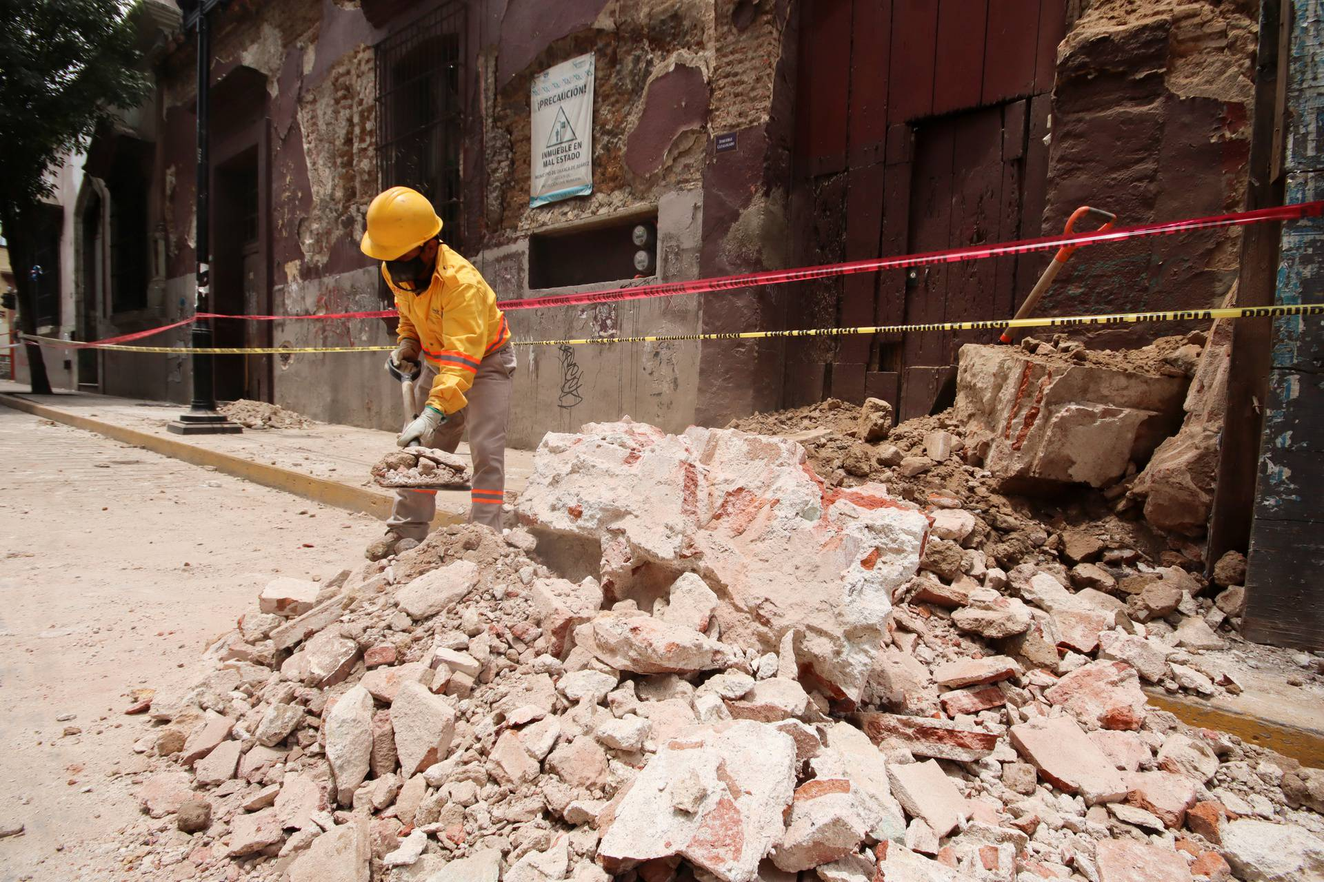 A worker removes debris from a building damaged during a quake, in Oaxaca
