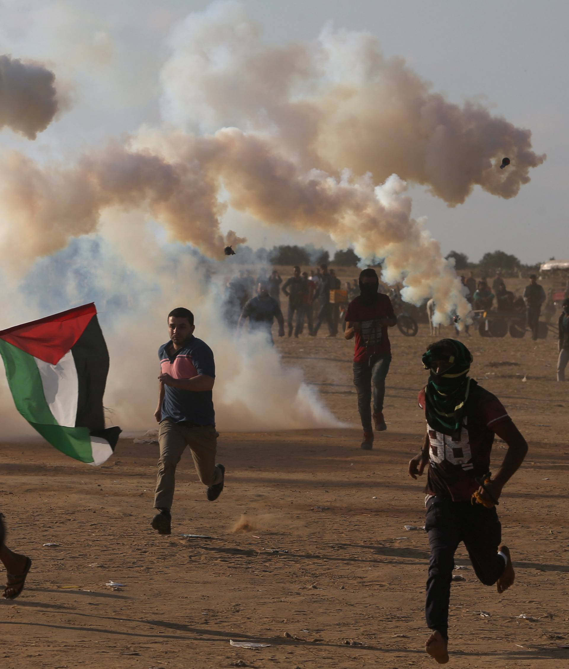 Palestinian demonstrators run from tear gas fired by Israeli troops during a protest marking the 70th anniversary of Nakba, at the Israel-Gaza border in the southern Gaza Strip