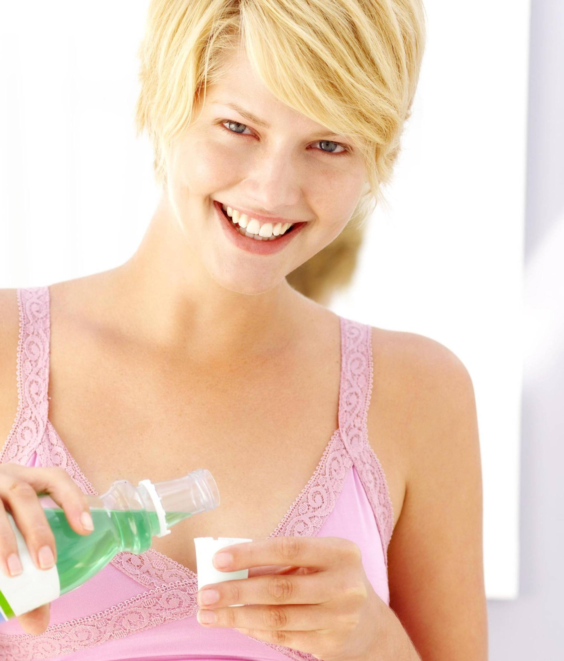portrait of a woman taking mouthwash in a cup