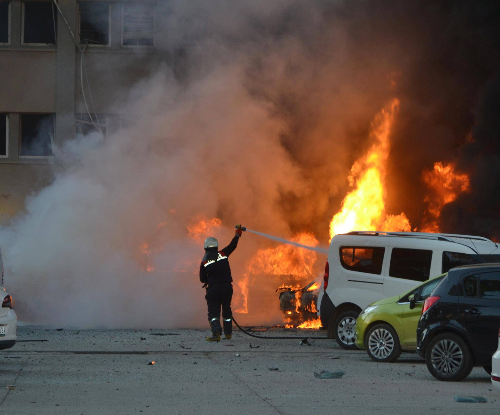 A firefighter tries to extinguish burning vehicles after an explosion outside the governor's office in the southern city of Adana