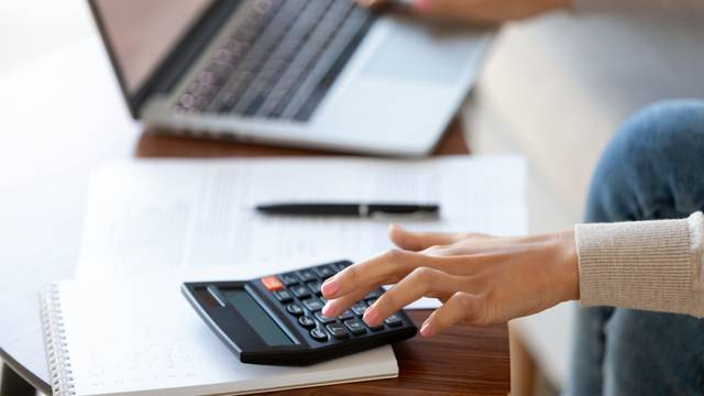 Businesswoman,Using,Calculator,And,Laptop,For,Budget,Cost,Money,Management
