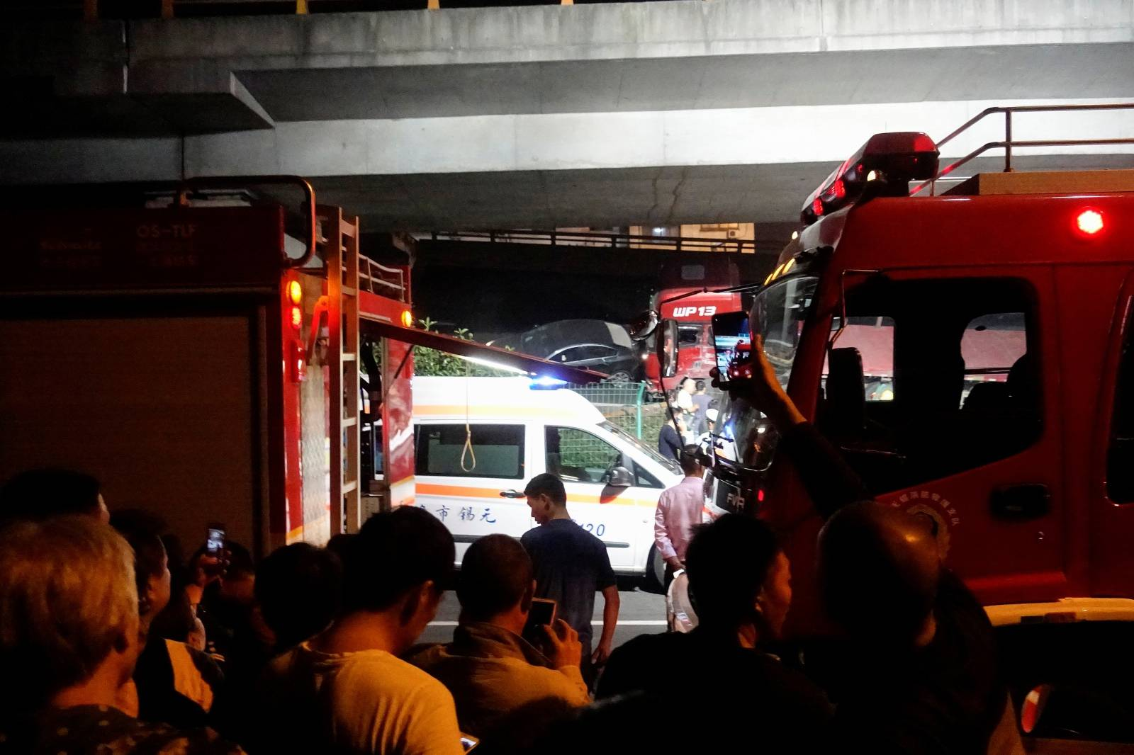 Rescue vehicles and ambulance are seen at the site after a part of highway overpass collapsed in Wuxi, Jiangsu