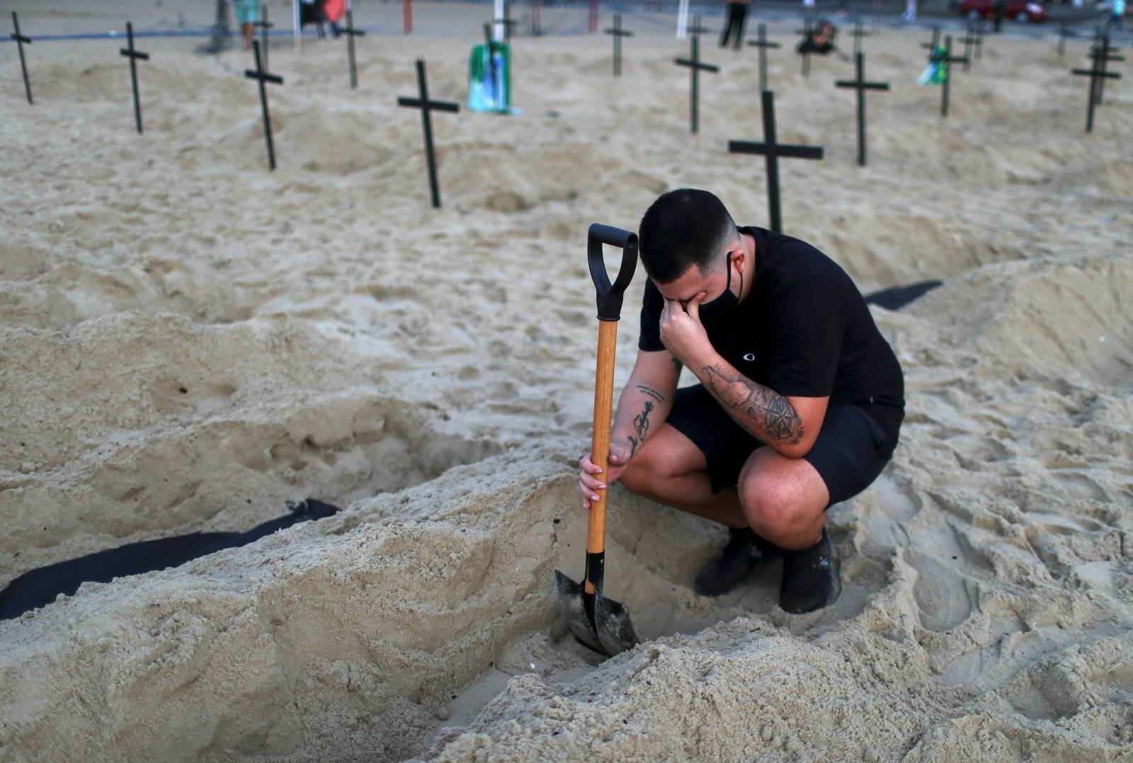 An activist of the NGO Rio de Paz wearing a protective mask reacts as he attends a demonstration during which one hundred graves were dug on Copacabana beach symbolising the dead from the coronavirus disease (COVID-19), in Rio de Janeiro