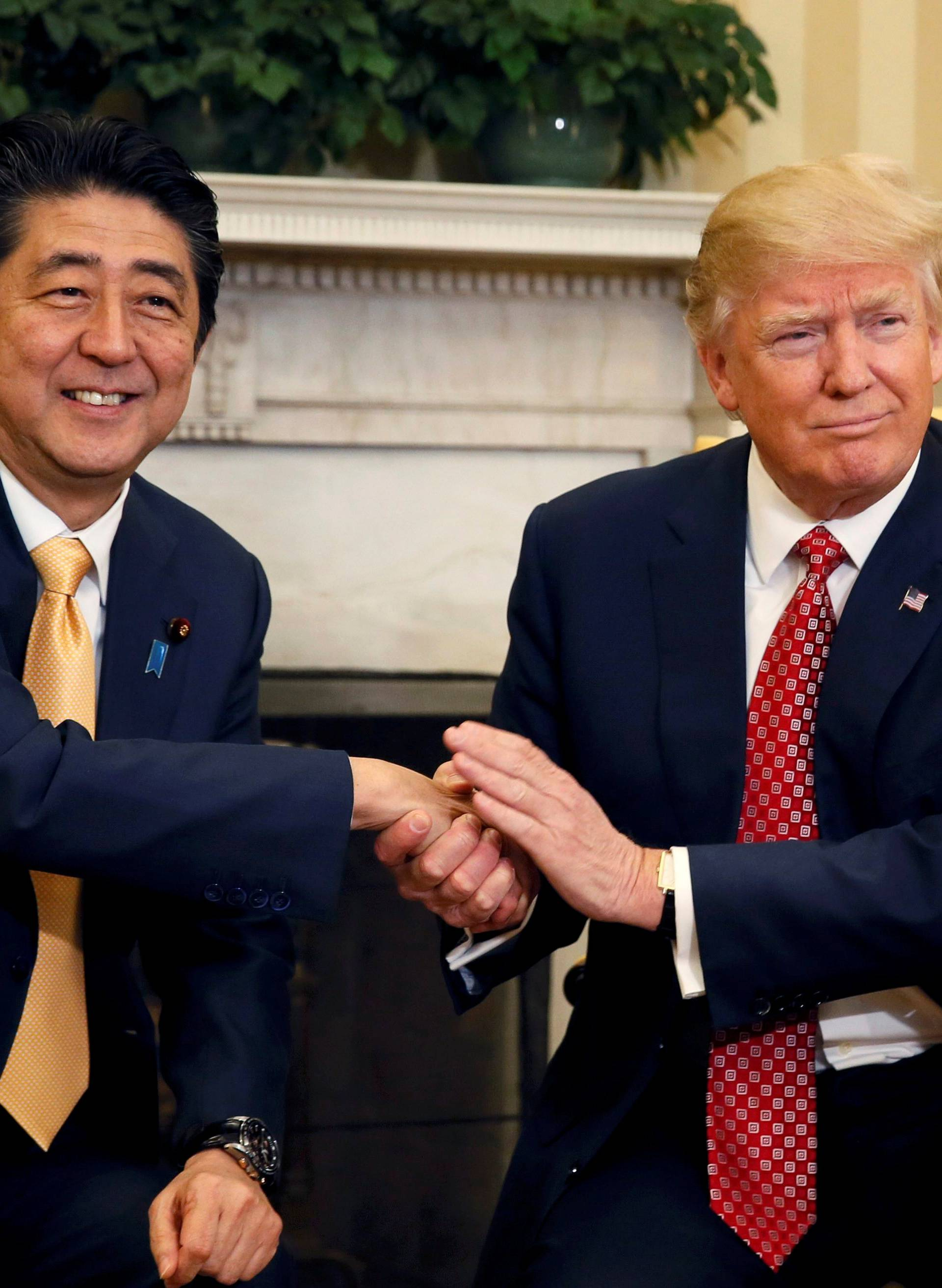 Japanese Prime Minister Abe shakes hands with U.S. President Trump during their meeting in the Oval Office at the White House in Washington
