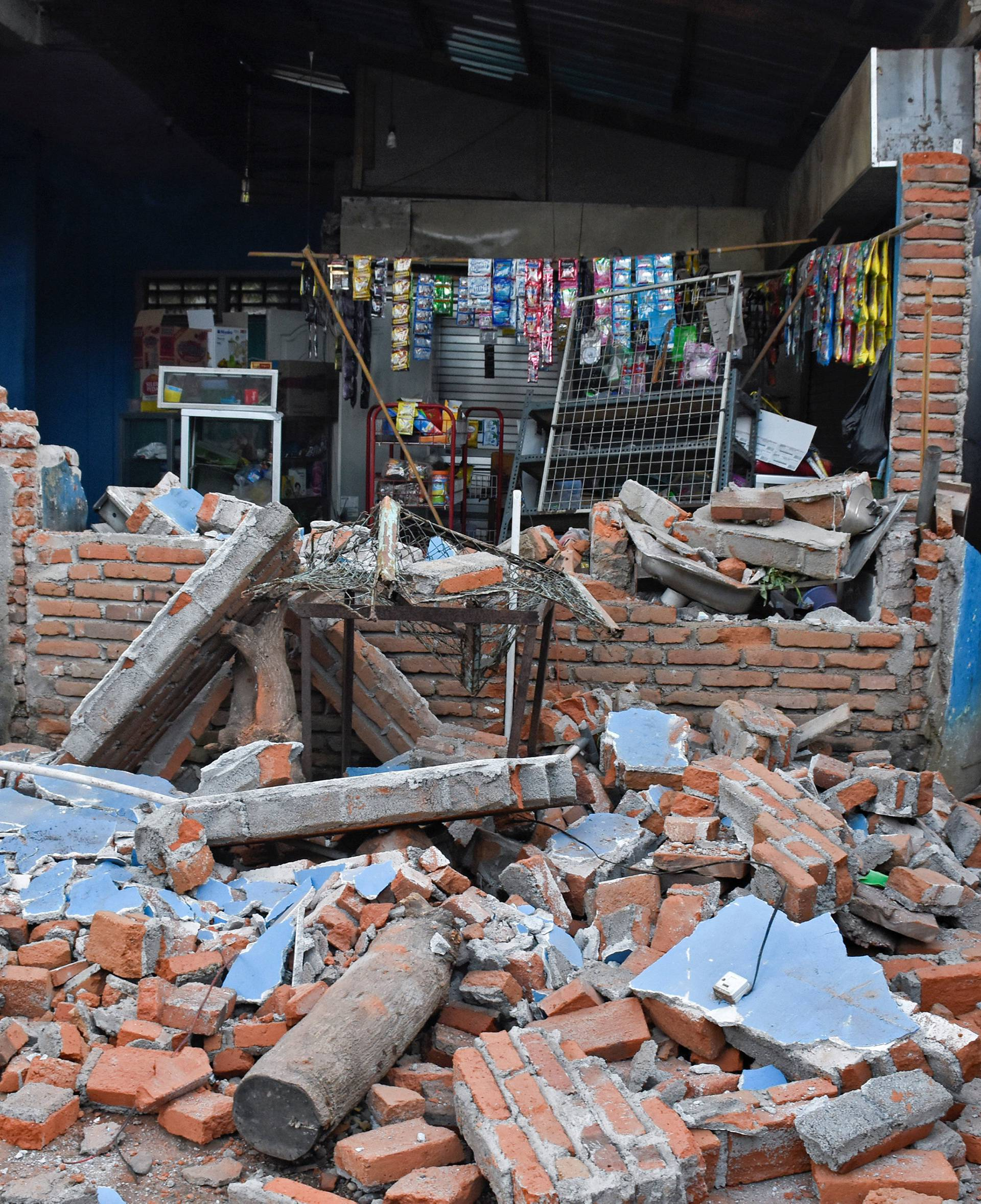 A woman walks past debris from a collapsed wall following a strong earthquake in Lendang Bajur Hamlet, Lombok