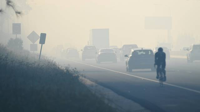 Motorists drive through smoke caused by bushfires on the M5 in Sydney