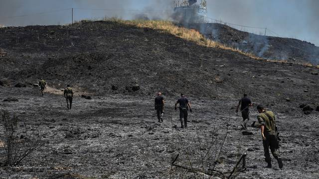 Israeli security forces inspect the area where fire broke out following a landing of a rocket that was fired at Israel from Lebanon, in Kiryat Shmona