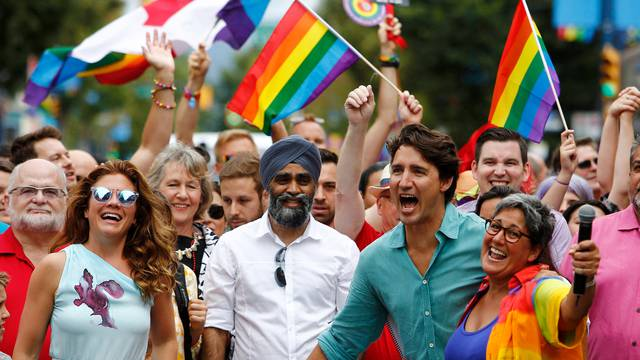 Canada's Prime Minister Justin Trudeau reacts as he and his wife Sophie Grégoire Trudeau (L) walk in the Vancouver Pride Parade