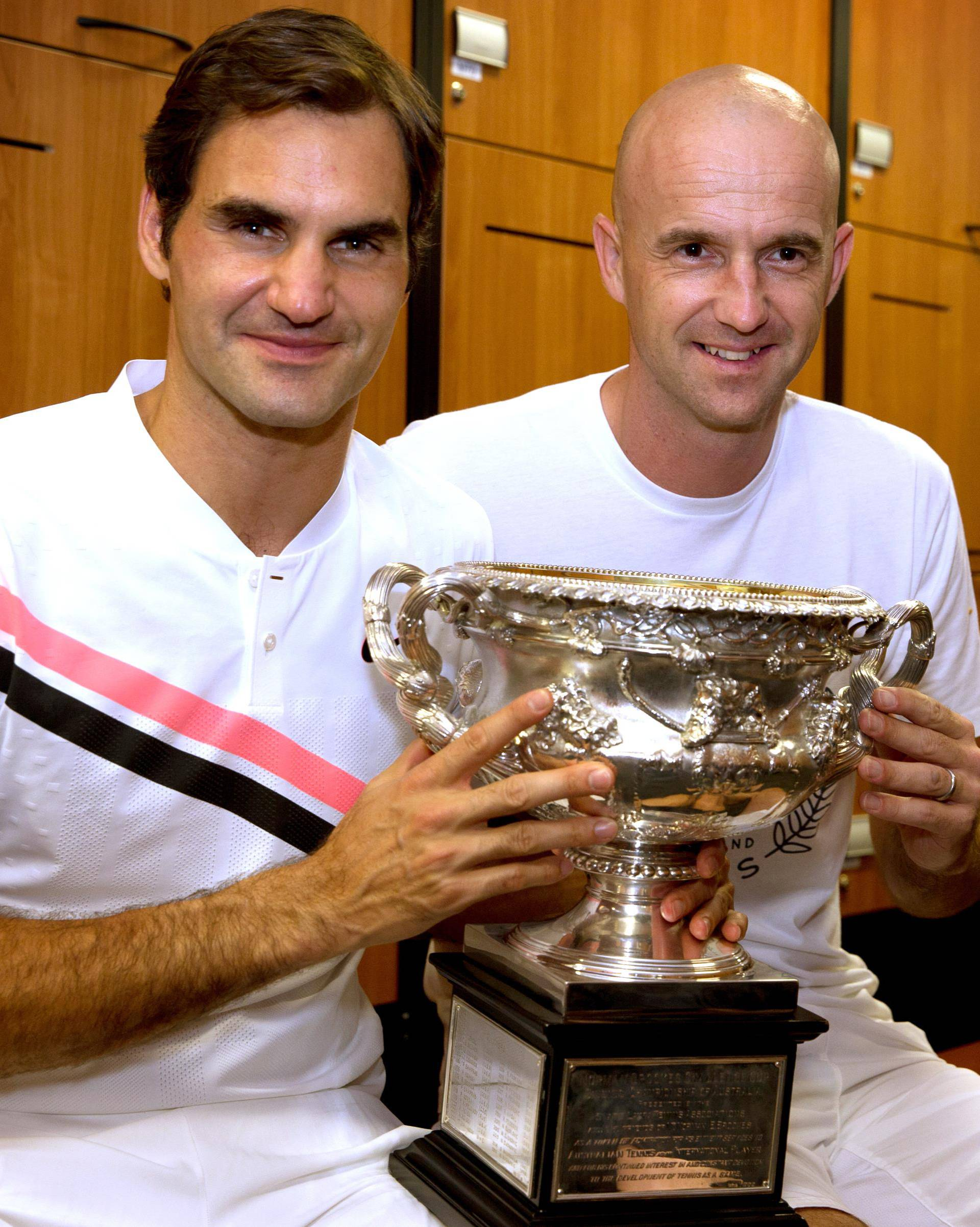 Roger Federer of Switzerland and his coach Ivan Ljubicic pose with the trophy after Federer won the Australian Open tennis tournament men's singles final, in the locker room in Melbourne
