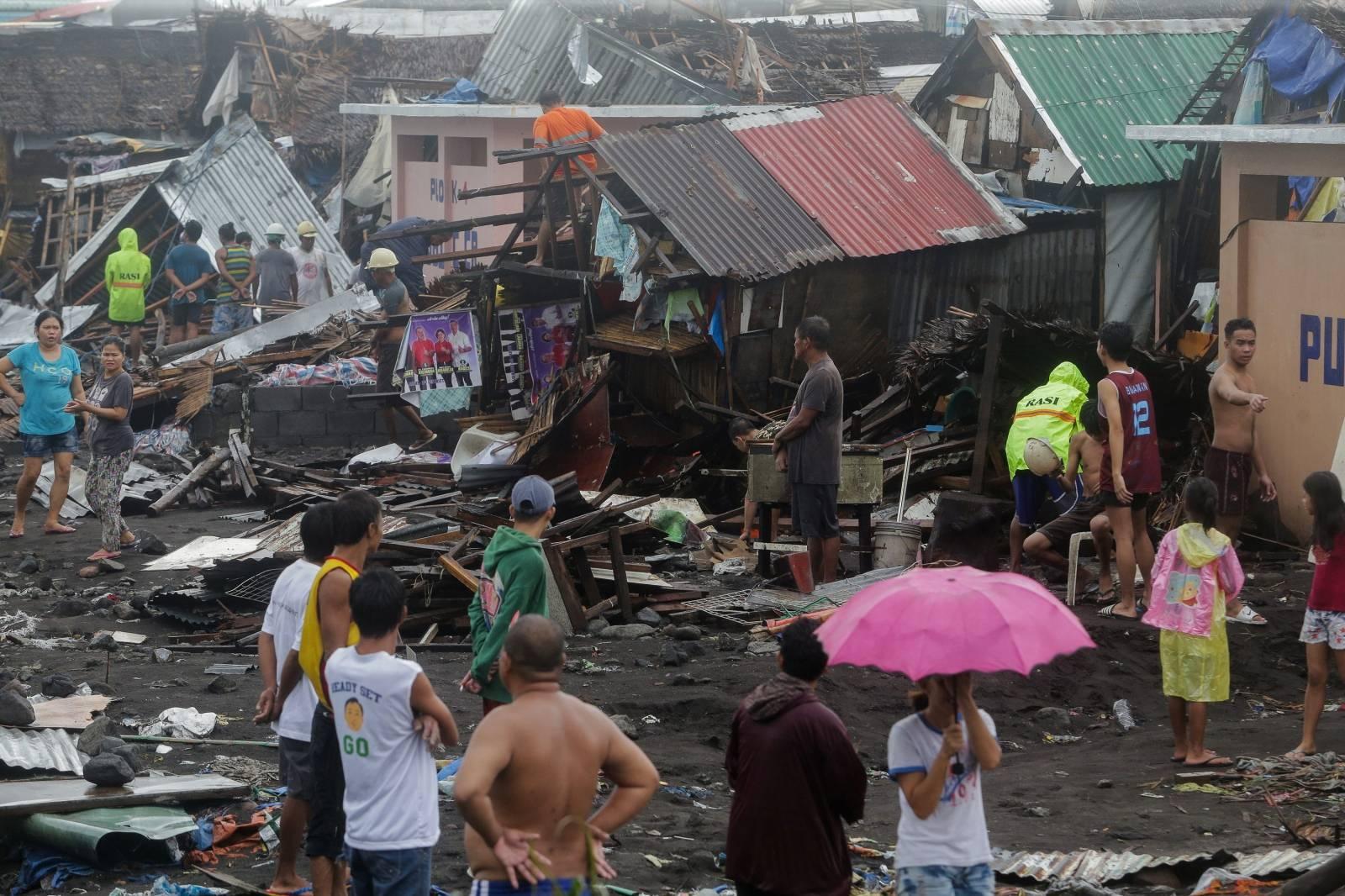 Residents stand among their damaged houses after Typhoon Kammuri hit Legazpi City, Albay