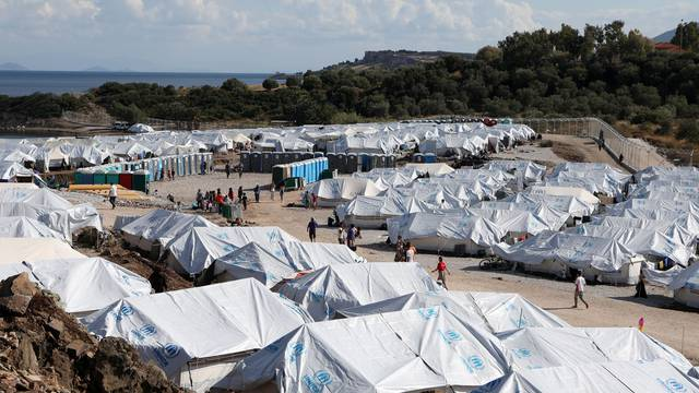 FILE PHOTO: Refugees and migrants make their way in the Kara Tepe camp on the island of Lesbos