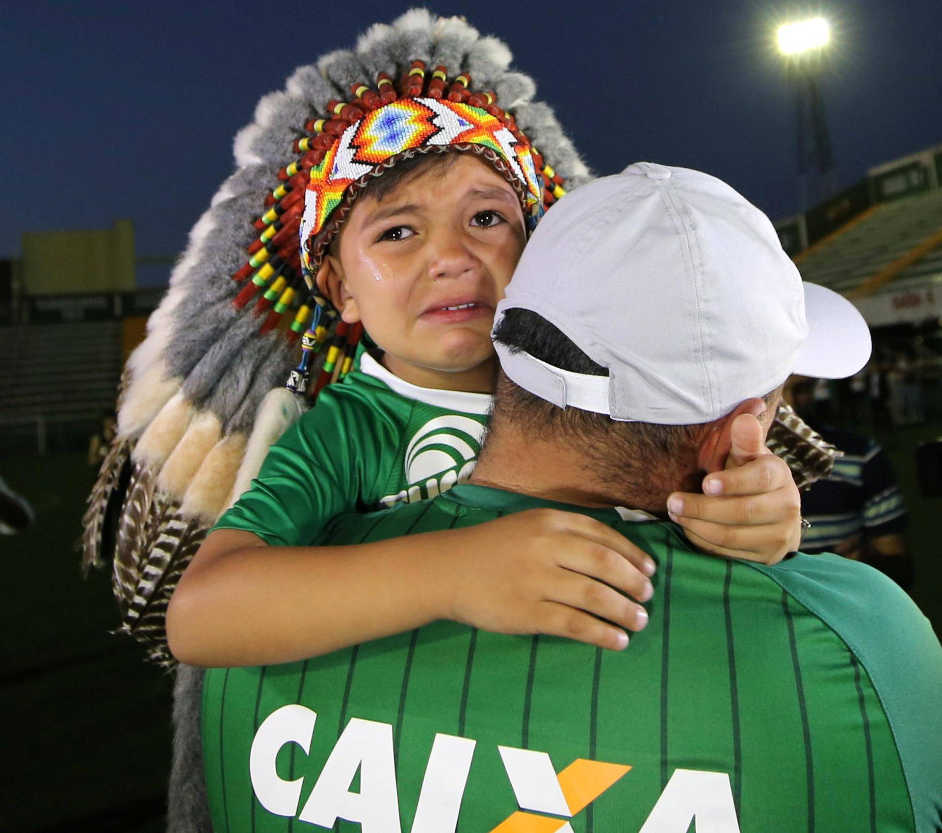 A fan of Chapecoense soccer team and his son react at the Arena Conda stadium in Chapeco