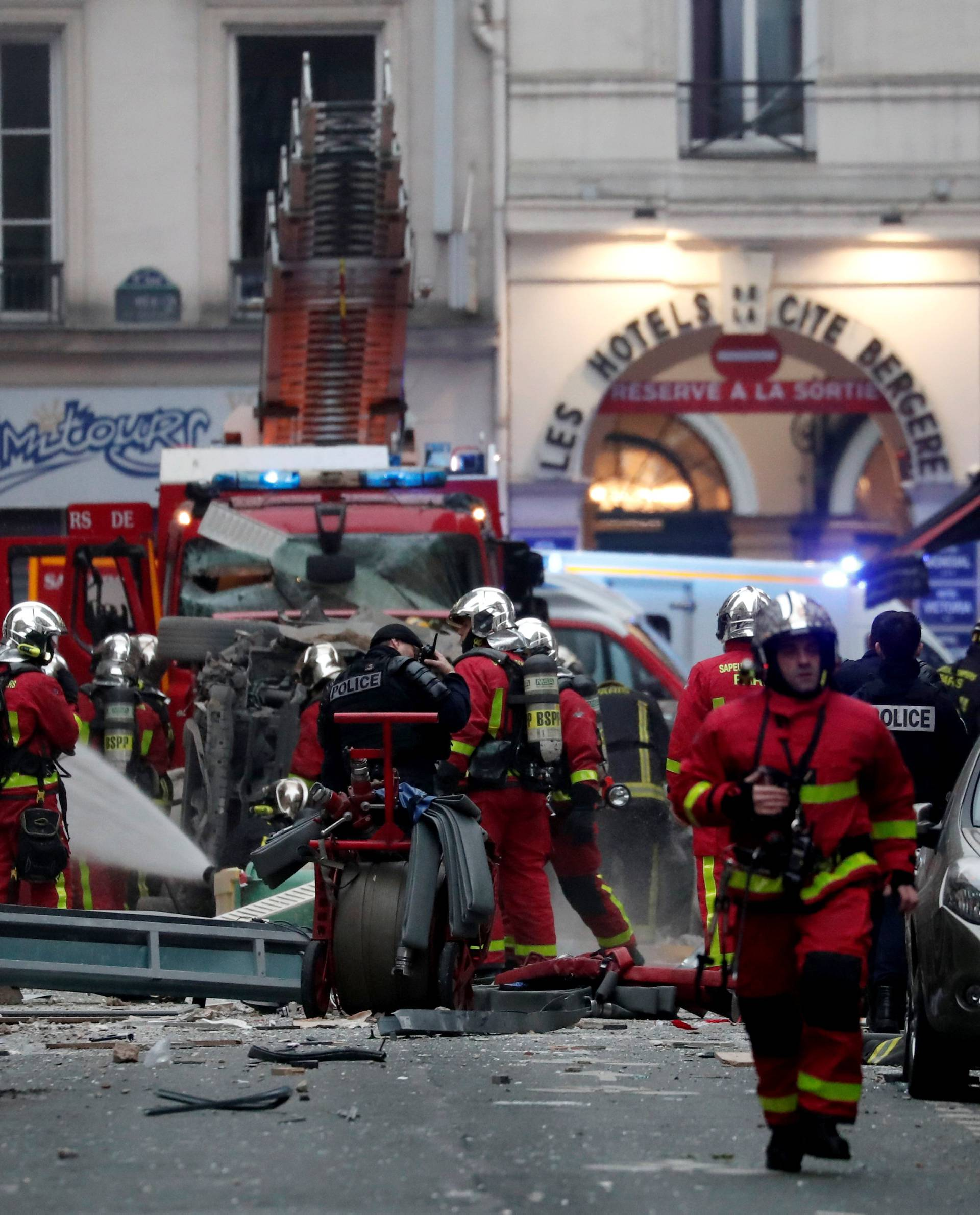 Firemen and police officers work at the site of an explosion in a bakery shop in the 9th District in Paris