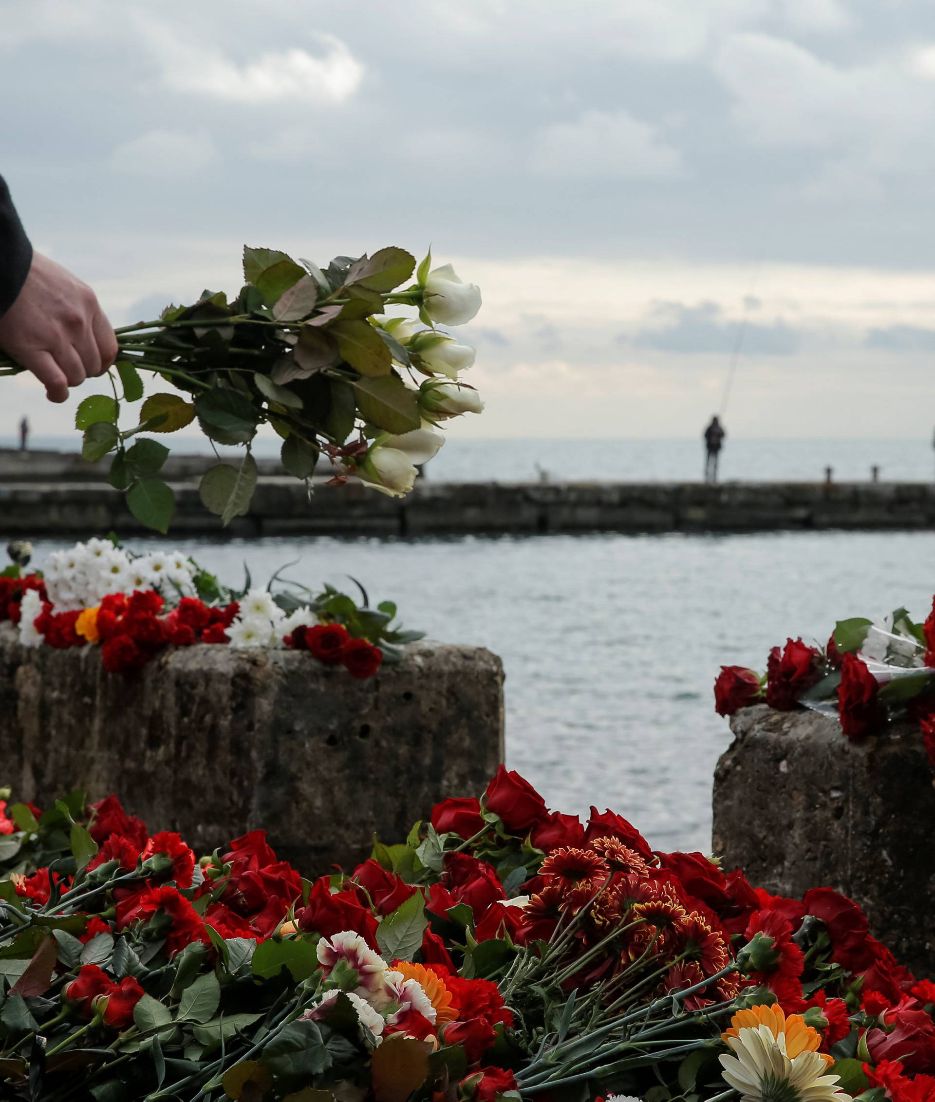 A person lays flowers in memory of passengers and crew members of Russian military Tu-154, which crashed into the Black Sea on its way to Syria on Sunday, at an embankment in the Black Sea resort city of Sochi