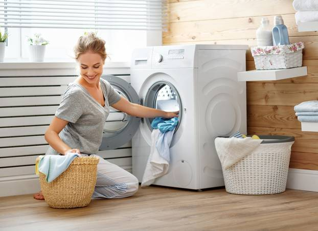 Happy housewife woman in laundry room with washing machine