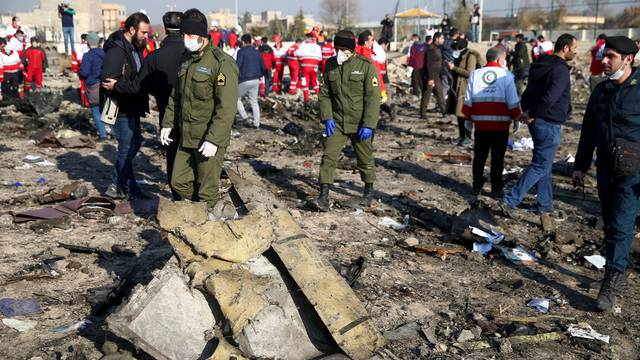 FILE PHOTO: Security officers and Red Crescent workers are seen at the site where the Ukraine International Airlines plane crashed after take-off from Iran's Imam Khomeini airport, on the outskirts of Tehran