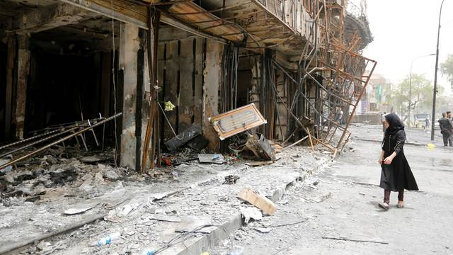 A girl walks past the site after a suicide car bomb attack at the shopping area of Karrada, a largely Shi'ite district, in Baghdad