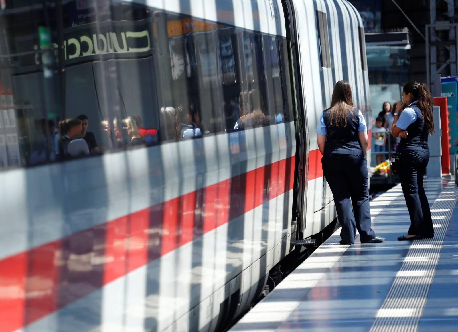 Deutsche Bahn employees stand next to an ICE high-speed train at the main train station in Frankfurt