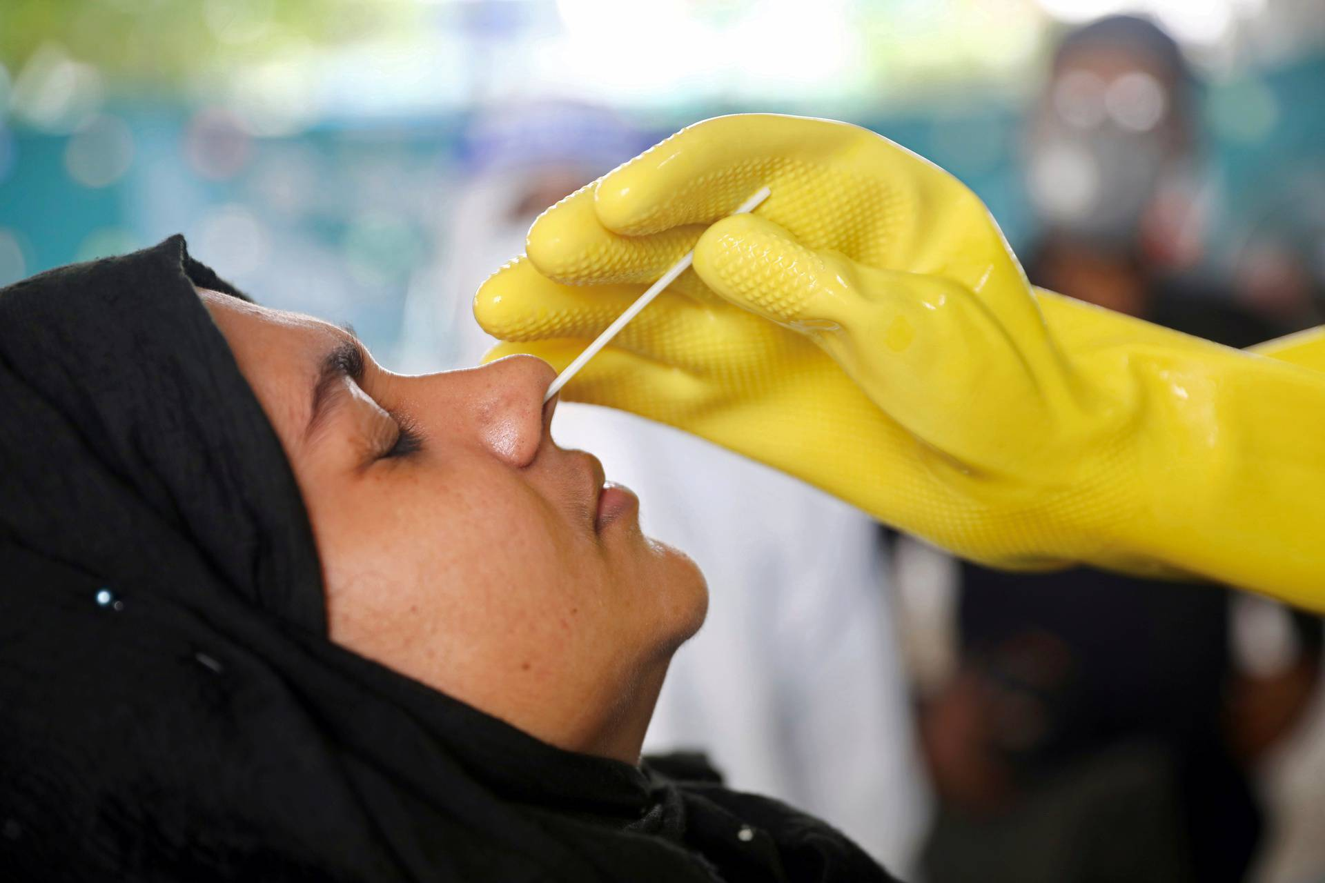 Health worker collects swab sample from woman at Mugda Medical College and Hospital in Dhaka