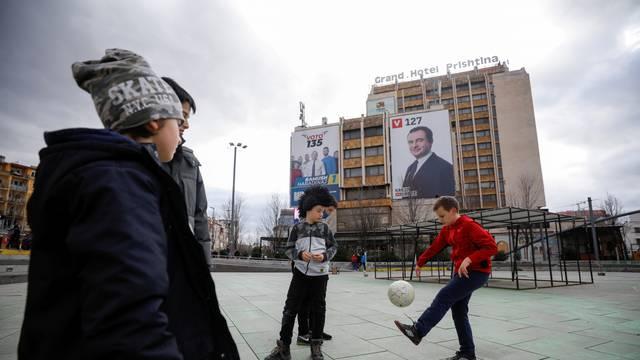 Children play football near electoral campaign billboards in Pristina, Kosovo